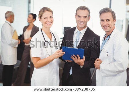 Portrait of happy medical team with clipboard in hospital