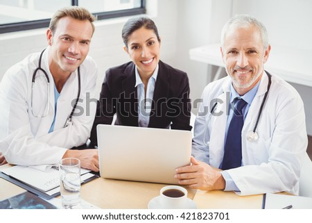 Portrait of happy medical team with laptop in conference room in hospital