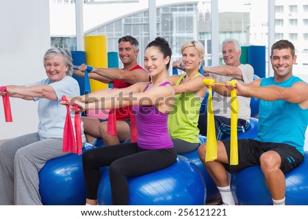 Portrait of happy men and women on fitness balls exercising with resistance bands in gym - stock photo