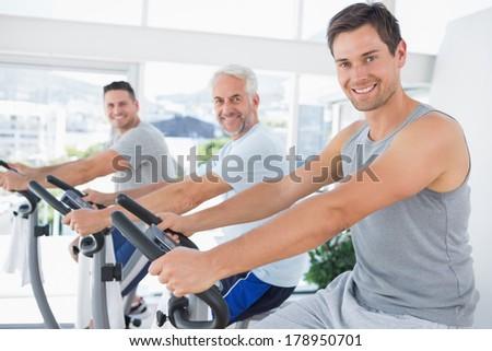 Portrait of happy men on exercise bikes at fitness studio - stock photo