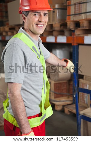 Portrait of happy mid adult foreman holding handtruck at warehouse - stock photo