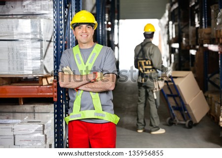 Portrait of happy mid adult foreman with arms crossed and coworker pushing handtruck at warehouse