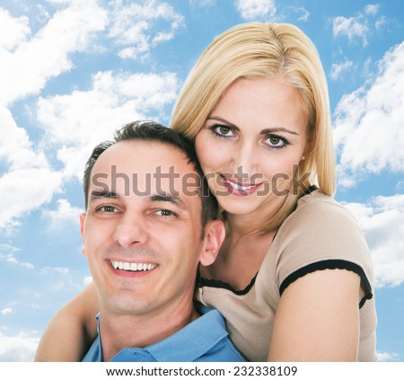 Portrait of happy mid adult man giving piggyback ride to woman against sky - stock photo