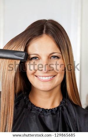 Portrait of happy mid adult woman straightening hair - stock photo