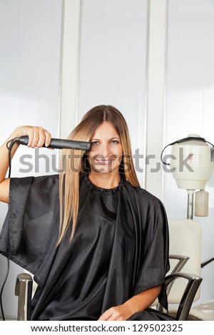 Portrait of happy mid adult woman straightening her hair while sitting on chair - stock photo