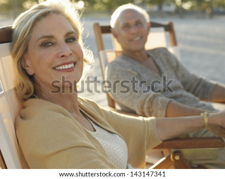 Portrait of happy middle age woman with man relaxing on deckchairs at beach - stock photo