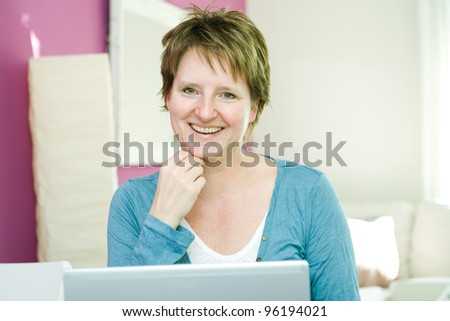Portrait of happy middle age woman with notebook at home smiling at camera - stock photo