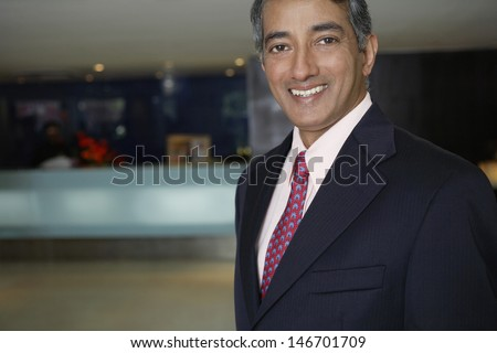 Portrait of happy middle aged businessman at hotel lobby - stock photo