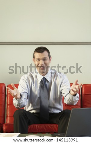 Portrait of happy middle aged businessman gesturing while sitting on red couch in office - stock photo
