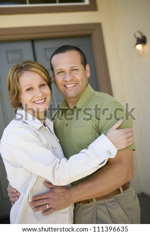 Portrait of happy middle aged couple in front of new house - stock photo