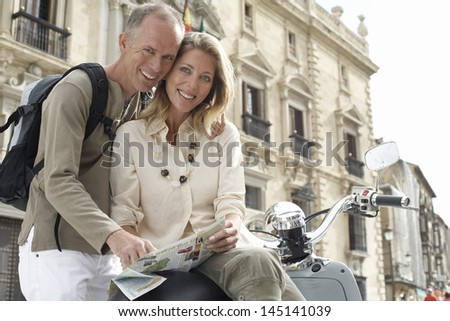 Portrait of happy middle aged couple with scooter reading map in front of building - stock photo