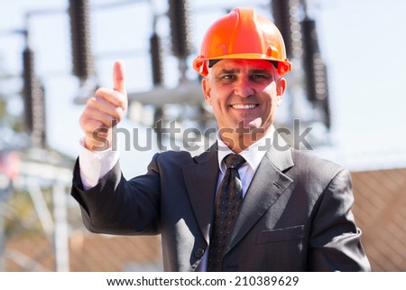 portrait of happy middle aged male industrial manager giving thumb up at substation - stock photo