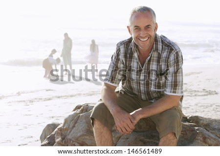 Portrait of happy middle aged man sitting on rock while family enjoying in background at beach - stock photo