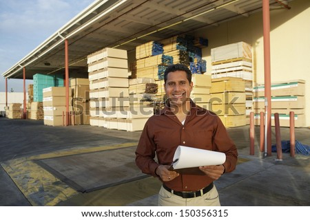 Portrait of happy middle aged man with clipboard standing in front of timber factory - stock photo