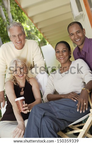 Portrait of happy middle aged multiethnic couples sitting together outdoors - stock photo