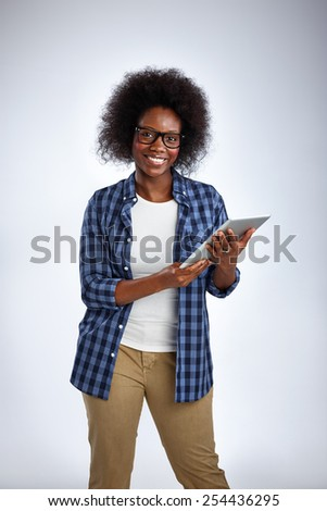 Portrait of happy middle aged woman with a digital tablet in studio looking at camera - stock photo