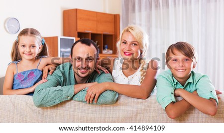 Portrait of happy middle class caucasian family at home. Focus on man - stock photo