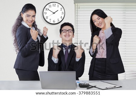 Portrait of happy mixed race businesspeople celebrating their success in the office room