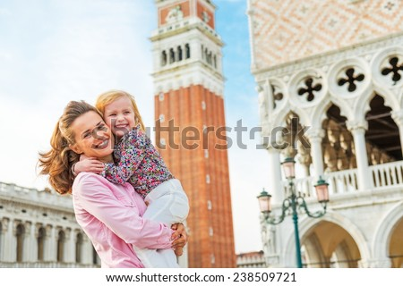 Portrait of happy mother and baby against campanile di san marco in venice, italy - stock photo