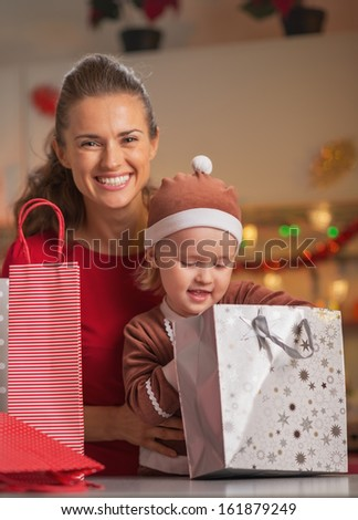 Portrait of happy mother and baby checking christmas shopping bags - stock photo