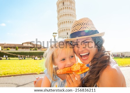 Portrait of happy mother and baby girl eating pizza in front of leaning tower of pisa, tuscany, italy - stock photo