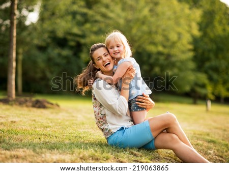Portrait of happy mother and baby girl hugging in park - stock photo