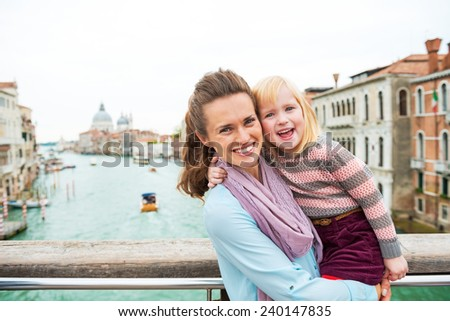 Portrait of happy mother and baby girl on bridge with grand canal view in venice, italy - stock photo