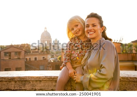 Portrait of happy mother and baby girl on street overlooking rooftops of rome on sunset