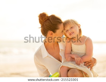 Portrait of happy mother and baby girl on the beach in the evening - stock photo