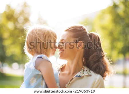 Portrait of happy mother and baby girl outdoors - stock photo