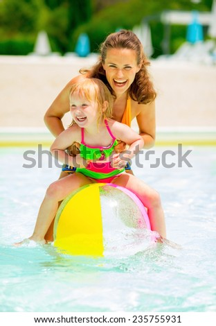 Portrait of happy mother and baby girl playing with beach ball in pool - stock photo