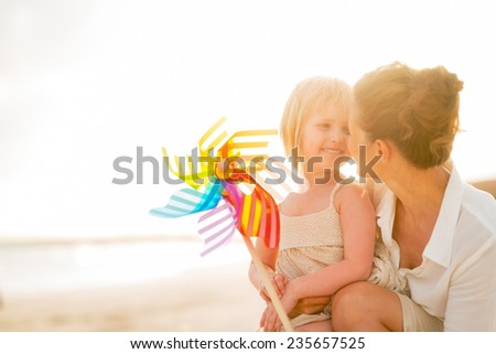 Portrait of happy mother and baby girl with colorful windmill toy on beach at the evening - stock photo