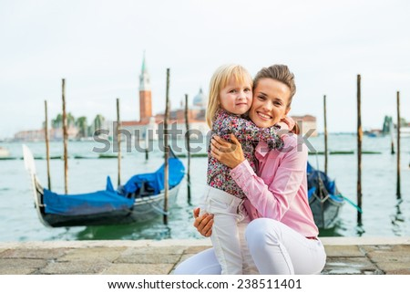 Portrait of happy mother and baby hugging on grand canal embankment in venice, italy - stock photo