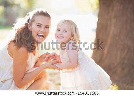 Portrait of happy mother and baby in park - stock photo
