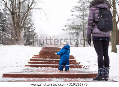 Portrait of happy mother and baby in winter park  - stock photo