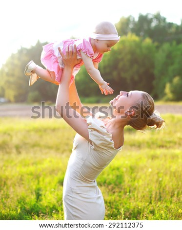 Portrait of happy mother and baby little daughter wearing a dress having fun together in sunny summer day  - stock photo
