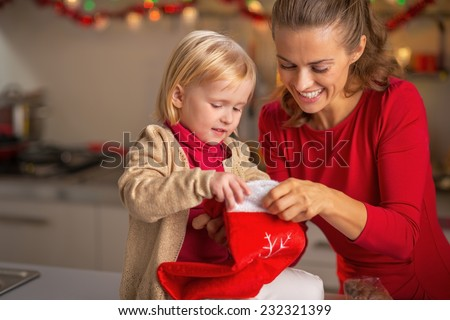 Portrait of happy mother and baby with christmas stocking in kitchen - stock photo