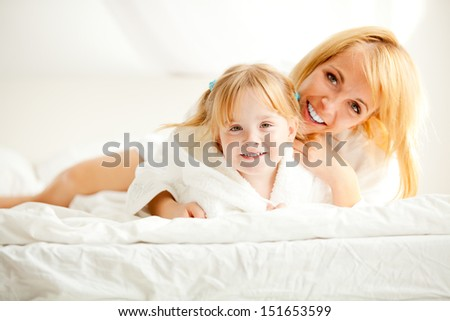 Portrait of happy mother and child lying on bed over white