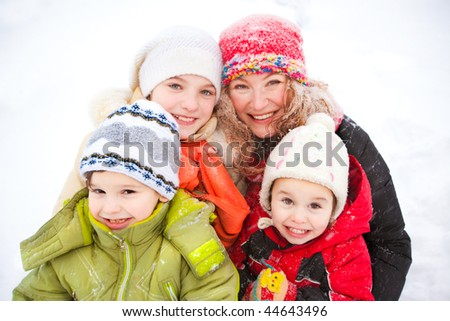 Portrait of happy mother and children together in snow on a cold winter day laughing, smiling - stock photo