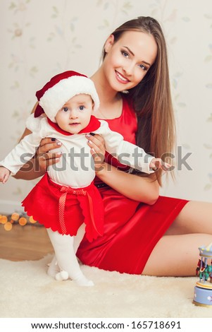 Portrait of happy mother and cute baby in suit of Santa's little helper