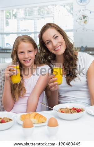 Portrait of happy mother and daughter having breakfast in the kitchen at home