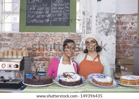 Portrait of happy mother and daughter in aprons standing at cake shop counter - stock photo