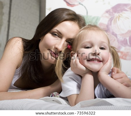portrait of happy mother and daughter in bed