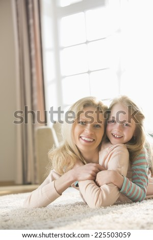 Portrait of happy mother and daughter lying on floor at home - stock photo
