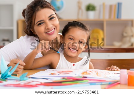 Portrait of happy mother and daughter painting with gouache - stock photo