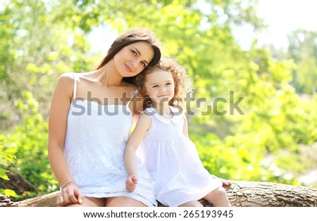 Portrait of happy mother and daughter together outdoors in sunny summer day - stock photo