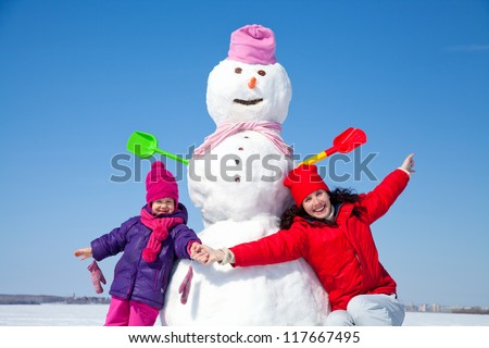 Portrait of happy mother and daughter with big snowman blue sky background