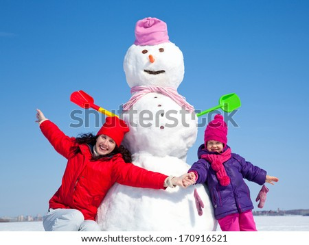 Portrait of happy mother and daughter with big snowman blue sky background - stock photo