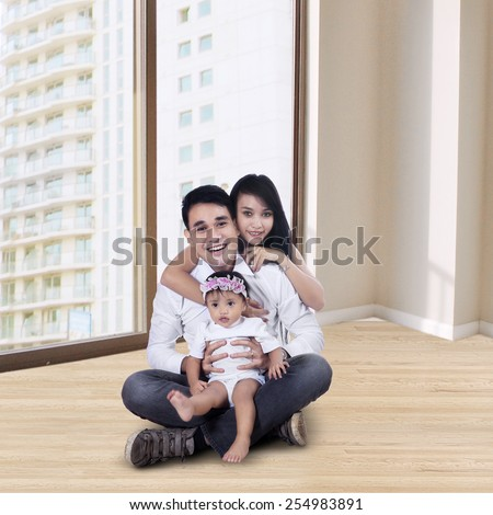 Portrait of happy mother and father with little baby sitting on the new apartment - stock photo