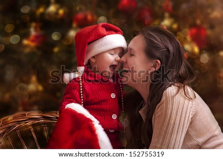 Portrait of happy mother and litle baby in santa's hats - stock photo